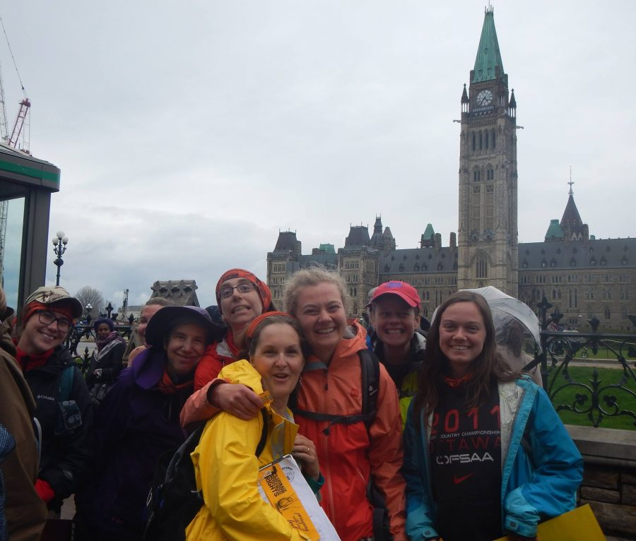 Erin Froese (centre) with a group of fellow smiling walkers in from the Parliament buildings in Ottawa, Ontario, having successfully reached their destination.