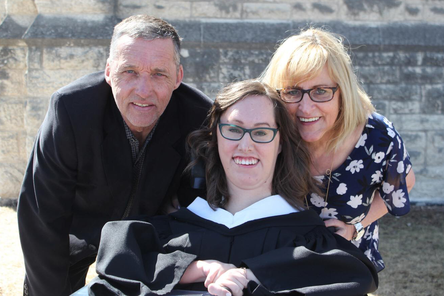 Cristina Waldner in her graduation gown surrounded by her parents on the day of her graduation from CMU.