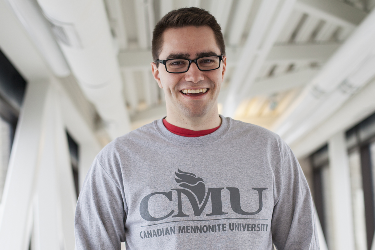 Jason Friesen - The courage to be vulnerable (Portrait of Jason Friesen on the Marpeck bridge wearing a grey long sleeved t-shirt with the CMU logo across the chest.)
