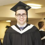 Jason Friesen wearing his black graduation cap and gown on the day of his graduation from CMU's Communications and Media program.