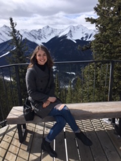 Anika Loeppky sits on a bench with white rocky mountain peaks in the background.