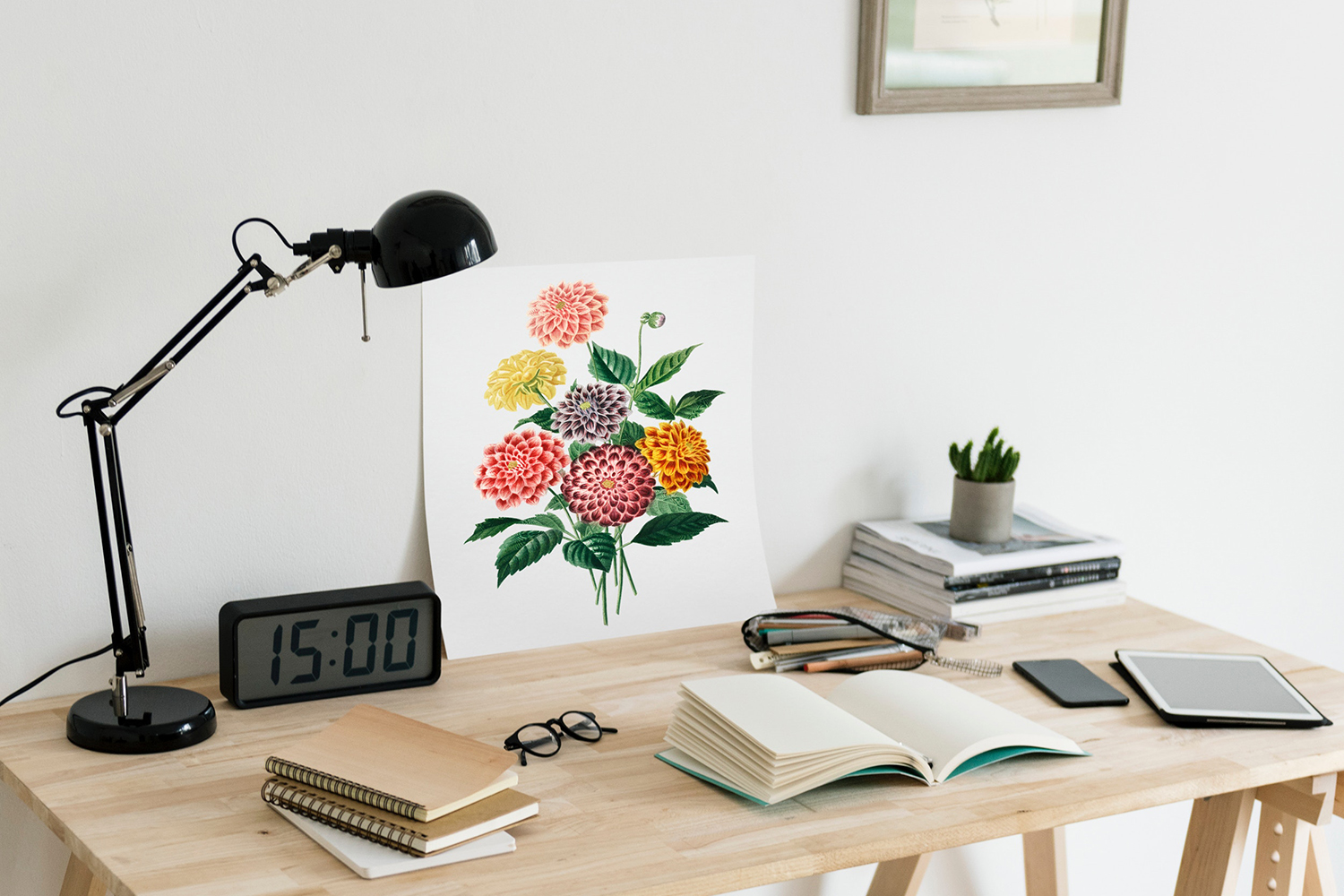 "6 study tips — A modern wood desk topped with a black desk lamp, a large digital clock that reads ""15:00"", a colourful painting of a bouquet of flowers, several notebooks, a pair of glasses, a pencil case with highlighters tumbling out, a cell phone and tablet, and in the corner a stack of books topped by a small succulent plant."